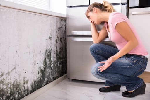 woman sees mold on wall